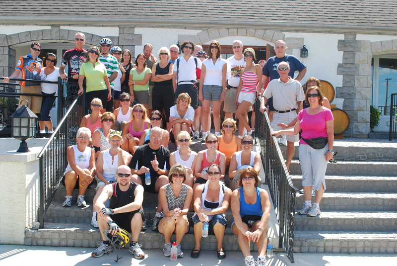Participants on the Wine Trail Ride take a moment to pose together in front of Pelee Island Winery