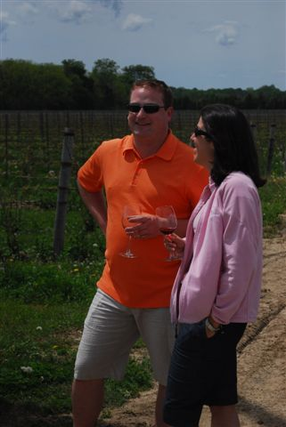 A couple enjoys some wine in the vineyard at Mastronardi Estate Winery