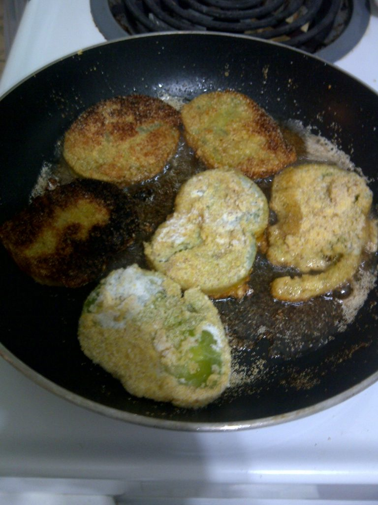 The green tomatoes coated and being fried