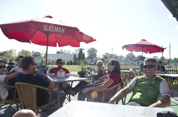 Participants of a Wine Trail Ride cycling tour enjoy the patio at Mettawas Station in Kingsville, Ontario