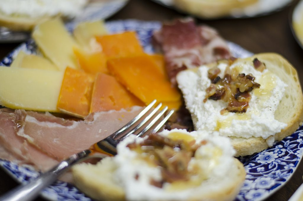 Bacon Honey Ricotta Crostini plated with cured meats and gourmet cheeses
