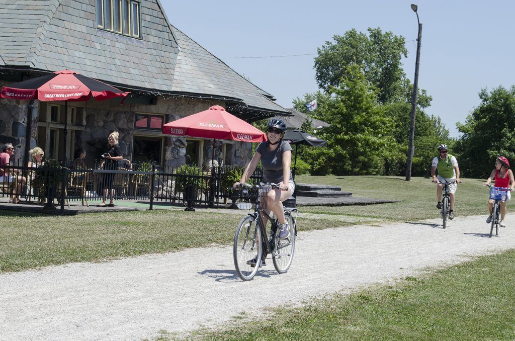 Wine Trail Ride cyclists riding by the Mettawas Station patio on the Greenway